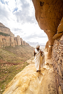 Priest holding the hand cross on rocks outside Abuna Yemata Guh church, Gheralta Mountains, Tigray Region, Ethiopia, Africa