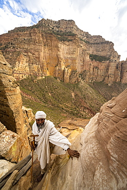 Ethiopian priest leaning on steep rocks leading to Abuna Yemata Guh church, Gheralta Mountains, Tigray Region, Ethiopia, Africa