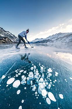 Man playing ice hockey on frozen Lake Sils, Engadine, canton of Graubunden, Switzerland, Europe