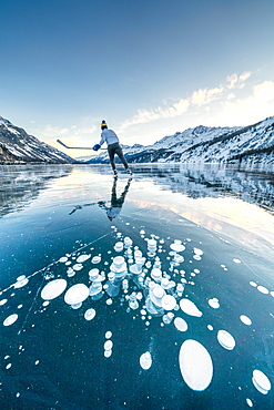 Ice hockey player skating on frozen Lake Sils covered of bubbles, Engadine, canton of Graubunden, Switzerland, Europe