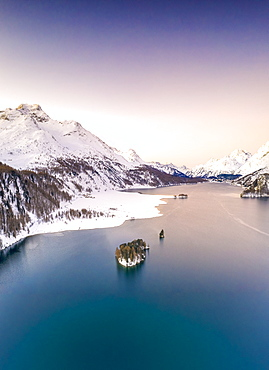 Aerial by drone of Lake Sils surrounded by snowy peaks during a winter sunrise, Engadine, canton of Graubunden, Switzerland, Europe