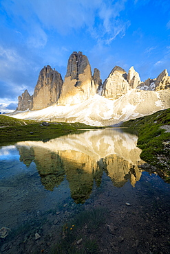 Sunset over Tre Cime di Lavaredo mirrored in Grava Longa lakes, Sesto Dolomites Natural Park, South Tyrol, Italy, Europe