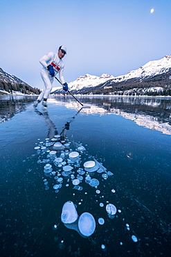 Ice hockey player man skating on Lake Sils covered in  ice bubbles at dusk, Engadine, Graubunden canton, Switzerland, Europe