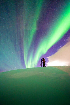 Man with tripod photographing the Northern Lights (Aurora Borealis) standing in the snow, Skarsvag, Nordkapp, Troms og Finnmark, Norway, Scandinavia, Europe
