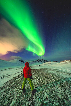 Man standing in the icy landscape admiring the Northern Lights (Aurora Borealis), Mageroya island, Nordkapp, Troms og Finnmark, Norway, Scandinavia, Europe