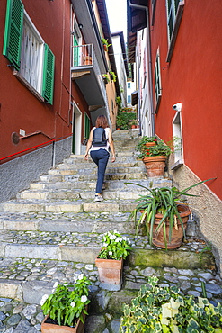 Rear view of woman walking up flight of steps in the old alley of Varenna, Lake Como, Lecco province, Lombardy, Italian Lakes, Italy, Europe