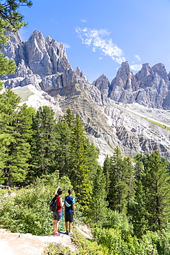 Rear view of two young hikers admiring the Odle from the famous Adolf Munkel trail, Val di Funes, South Tyrol, Dolomites, Italy, Europe
