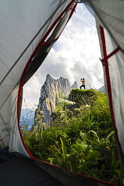 Man on rocks photographing Saxer Lucke mountain with smartphone seen from hiking tent, Appenzell Canton, Switzerland, Europe