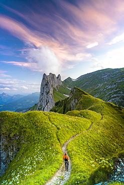 Hiker man walking on footpath towards Saxer Lucke at sunset, Appenzell Canton, Alpstein Range, Switzerland, Europe