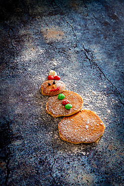 Cute decorated pancakes in shape of snowman on table background made by children for Christmas