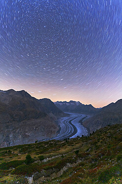 Star trail in the night sky above Aletsch Glacier, Bernese Alps, Valais canton, Switzerland