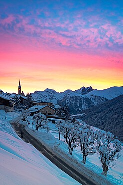 Sunrise on empty road towards the village of Guarda after a winter snowfall, Graubunden canton, Lower Engadin, Switzerland