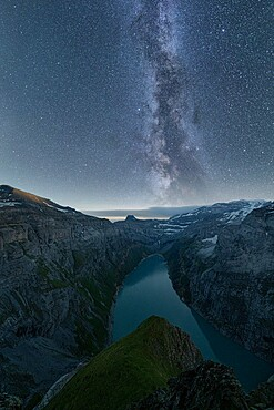 Milky Way in the starry night sky over lake Limmernsee, aerial view, Canton of Glarus, Switzerland, Europe