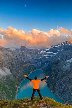 Man with outstretched arms enjoying sunset over lake Limmernsee standing on top of rocks, Canton of Glarus, Switzerland