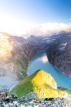 Aerial view of cheerful man with outstretched arms admiring lake Limmernsee at sunset, Canton of Glarus, Switzerland