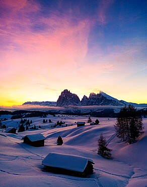 Mountain huts covered with snow at dawn with Sassopiatto and Sassolungo in background, Seiser Alm, Dolomites, South Tyrol, Italy, Europe