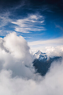 Sunlight over Weisshorn peak emerging from a sea of clouds, canton of Valais, Switzerland, Europe