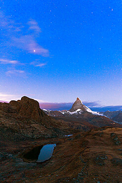 Starry sky before sunrise over Matterhorn and Riffelsee lake, Gornergrat, Zermatt, canton of Valais, Switzerland, Europe
