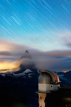Star trail in the night sky on Matterhorn from observatory tower of Kulmhotel Gornergrat, Zermatt, Valais canton, Switzerland, Europe