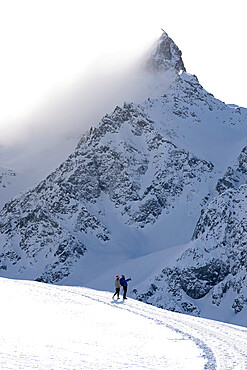 Tourists photographing the snowy peaks during a winter hike, Muottas Muragl, Samedan, Engadine, Graubunden canton, Switzerland, Europe