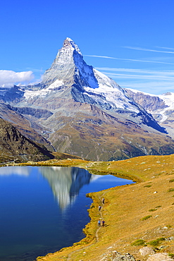 Hikers walking on the path beside the Stellisee with the Matterhorn reflected, Zermatt, Canton of Valais, Pennine Alps, Swiss Alps, Switzerland, Europe
