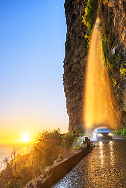 Car passing under Anjos waterfall on slippery coastal road at sunset, Ponta do Sol, Madeira island, Portugal