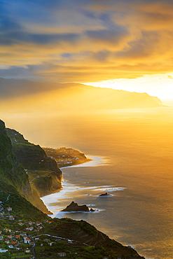 Burning sky at sunset over Arco de Sao Jorge and Ponta Delgada villages ocean front, Madeira island, Portugal