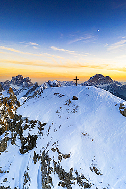 Sunset over the snowy peak of Nuvolau with Monte Pelmo and Civetta on background, aerial view, Dolomites, Veneto, Italy