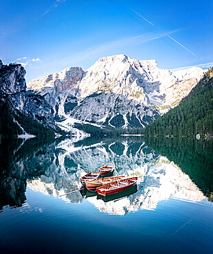 Boats moored in lake Braies (Pragser Wildsee) with mountains reflecting in water at sunrise, Dolomites, South Tyrol, Italy
