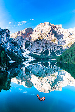 Lake Braies (Pragser Wildsee) with Croda del Becco reflecting in water at dawn, aerial view, Dolomites, South Tyrol, Italy