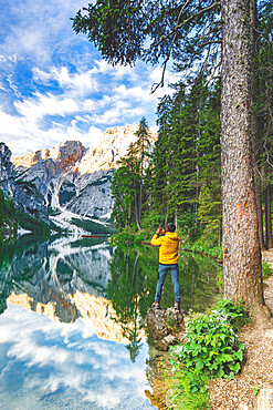 Hiker man photographing lake Braies (Pragser Wildsee) with smartphone at sunrise, Dolomites, South Tyrol, Italy
