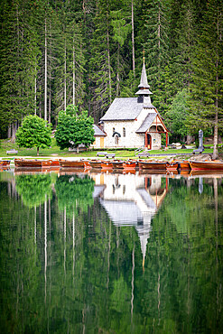 Green forest and chapel perfectly reflected in lake Braies / Pragser Wildsee in summer, Dolomites, South Tyrol, Italy
