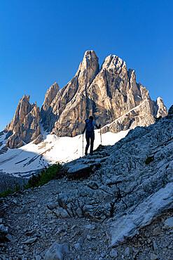 Silhouette of woman on path with Croda Dei Toni mountain on background, Val Fiscalina, Sesto Dolomites, South Tyrol, Italy
