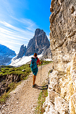 Backpacker woman with hiking poles enjoying the view to Croda Dei Toni from path, Sesto Dolomites, South Tyrol, Italy