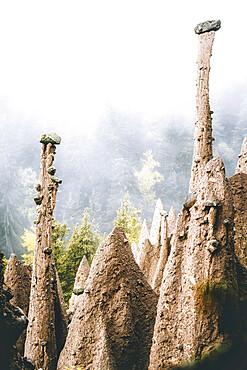 Foggy sky over the earth pyramids ancient rock formation, Renon/Ritten, Bolzano, South Tyrol, Italy