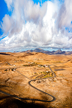 Scenic clouds on winding road running through desert mountains, aerial view, Tefia, Fuerteventura, Canary Islands, Spain