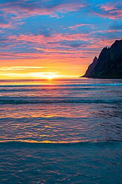 Burning sky of midnight sun reflecting in the sea, Ersfjord, Senja, Troms county, Norway