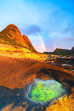 Algae inside rock formation on cliffs lit by rainbow during the midnight sun, Tungeneset, Senja, Troms county, Norway