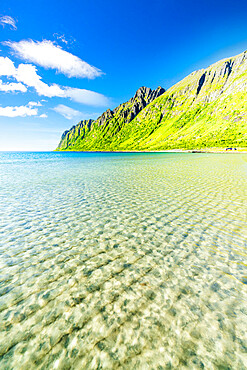 White sand washed by turquoise clear sea with mountains on background, Ersfjord beach, Senja, Troms county, Norway