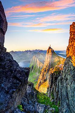 Hiker man admiring sunrise standing on top of Husfjellet mountain, Senja, Troms county, Norway