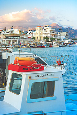 Fishing boats moored in the harbor of the seaside town of Ierapetra at sunset, Crete, Greece