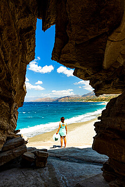 Rear view of young woman admiring the crystal sea from natural cave on Triopetra beach, Plakias, Crete, Greece