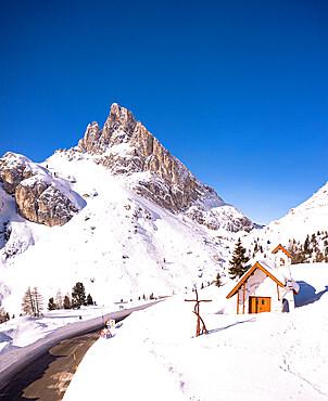 Alpine chapel in the snowy landscape with Sass de Stria peak on background, Falzarego pass, Belluno province, Veneto, Italy
