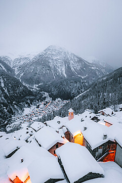 Mountain huts covered with snow in the alpine village of Starleggia, Campodolcino, Valchiavenna, Valtellina, Lombardy, Italy