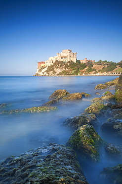 Alongside a picturesque millstone, atop a rocky promontory dominating the sea, rises the Castello di Falconara, Sicily, Italy, Mediterranean, Europe