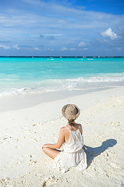 Woman sitting on a white sand beach enjoying the turquoise water, Sun Island Resort, Nalaguraidhoo island, Ari atoll, Maldives, Indian Ocean, Asia