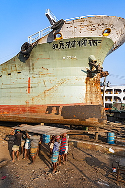 Men carrying a very heavy metal plate to the river, shipwreck cemetery (ship breaking yard), Port of Dhaka, Bangladesh, Asia