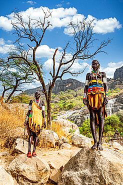 Traditional dressed young girls from the Laarim tribe standing on a rock, Boya hills, Eastern Equatoria, South Sudan