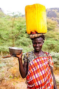 Woman with a water caniister on her head, Laarim tribe, Boya Hills, Eastern Equatoria, South Sudan, Africa