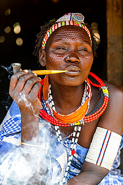 Woman with beauty scars from the Toposa tribe smoking a pipe, Eastern Equatoria, South Sudan, Africa